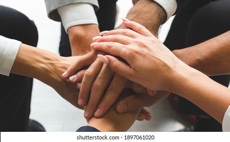 close up picture of hands of multiethnic business team touching in circle for sign of unity and integrity. togerther concept