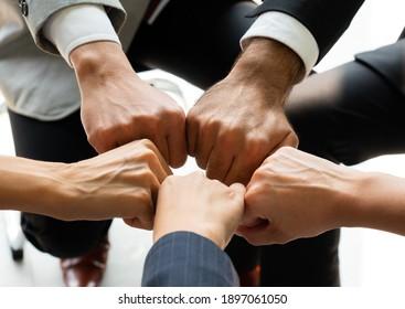 Nahaufnahme von Händen eines multiethnischen Geschäftsteams, das im Kreis um Zeichen der Einheit und Integrität greift. Gesamtkonzept