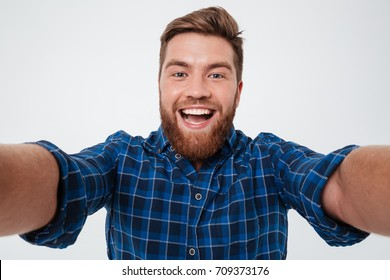 Close up picture of Happy bearded man in checkered shirt making selfie over gray background