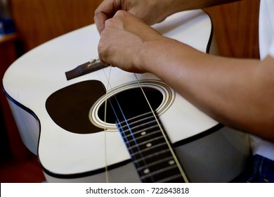 Close up picture of man changing strings in white acoustic guitar