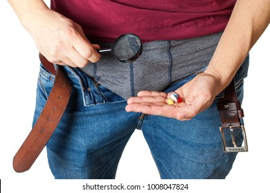 Close up picture of man's crotch with unzipped jeans holding potency pills and enlarged viewer