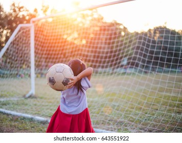Close up picture of an old ball and foot of a girl who is playing football in the sunshine day.