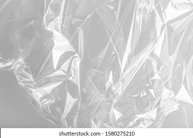 Close up picture on a plastic transparent cellophane bag on white background. The texture looks blank and shiny. The plastic surface is wrinkly and tattered making abstract pattern.