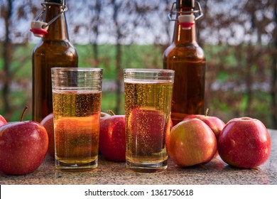 Close up Picture on two glasses or jars full of organic sparkling apple cider and two rustic bottles with red riped apples on stone garnit table in the garden restaurant during summer sunny evening.