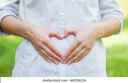 Close up picture of a pregnant woman showing a love sign on her belly in the first trimester, outdoor