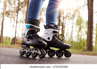 Close up picture of rollerblades, unknown person wearing rollerskates to spend time actively, black rollerblades with wheels being on road in fresh air, trying new purchase. Rollerskating concept.
