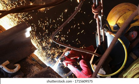 Close up picture of rope access abseiler worker wearing a fall industrial safety harness helmet, red welding safety leather glove dark face shield protection  commencing hot work gouging metal plate