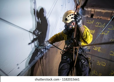 Close up picture of rope access painter wearing safety harness chemical mask working height hanging abseiling descending commencing spray painting in confined space construction site Perth, Australia
