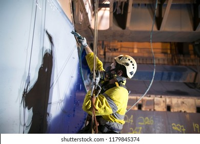 Close up picture of rope access technician wearing fully safety harness equipment a chemical spray mask protection descending abseiling commencing spraying blue painting job construction site, Perth