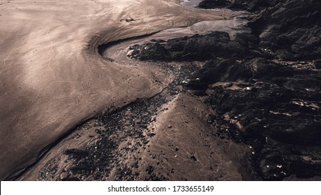 Close up picture of s shape trench curved by flowing water in sand around rocks on the beach.Light and shadows.Nature abstract.