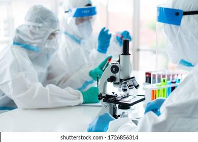 ein genaues Bild von Wissenschaftlern, die Persona tragen; Schutzausrüstung oder Einrichtung, die Mikroskop zum Experimentieren mit einem Covid-19- oder Coronavirus-Impfstoff im Labor verwendet. Wissenschaft und Medizin