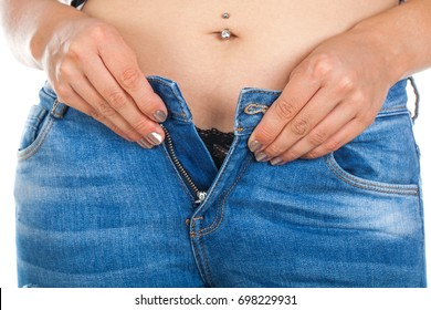 Close up picture of sexy woman's abdomen, belly ring, taking off her pants - on isolated background