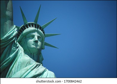 Close up picture of the Statue of Liberty (Liberty Enlightening the World) neoclassical sculpture against the blue sky on Liberty Island in New York City, USA