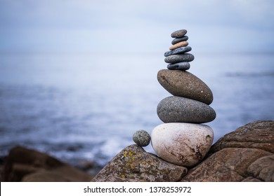 Close up picture of a stone cairn outdoors. Ocean in the blurry background