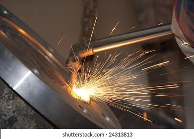 a close picture of a torch cutting steel