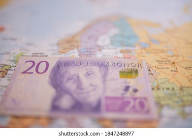 Close up picture of a twenty Swedish kronor banknote -with the words Twenty Kronor in Swedish- below Sweden on a colorful and blurry Europe map