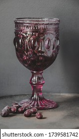 Close up picture of vintage colorful goblet glass in dark pink shade for wine or champagne drinks to celebrate with special design of table ware on black background as wallpaper concept with berries