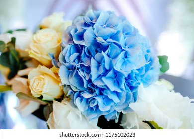 A close up picture of wedding flower arrangement with white roses and blue hydrangea.