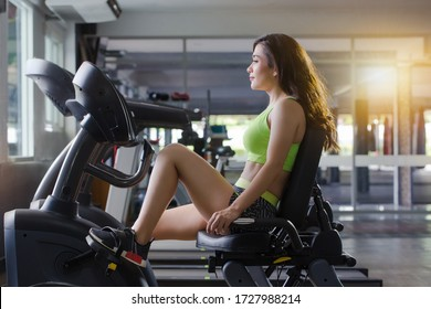 close up picture  the woman is exercise legs on a recumbent bike in the gym