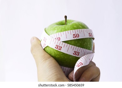 Close up picture of a woman holding a green apple and a measuring tape