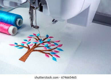 Close up picture workspace of  embroidery machine  show embroider tree design theme. And two thread s cyan and pink color.
