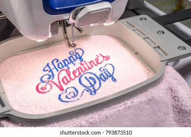 Close up picture of workspace embroidery machine embroidering text happy valentine on pink towel