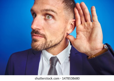 Close up picture of young handsome business man over blue isolated background smiling with hand over ear listening an hearing to rumor or gossip. Deafness concept.