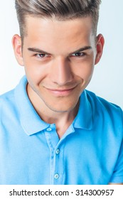 Close up picture of a young handsome man smiling at the camera.