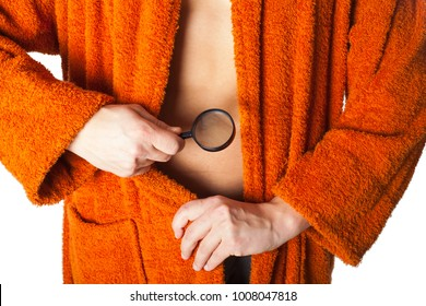Close up picture of young man wearing orange bathrobe checking his genitlas with enlarger glass