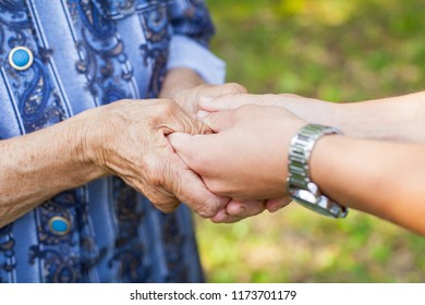 Close up picture of young woman holding her senior grandmother's wrinkled hands