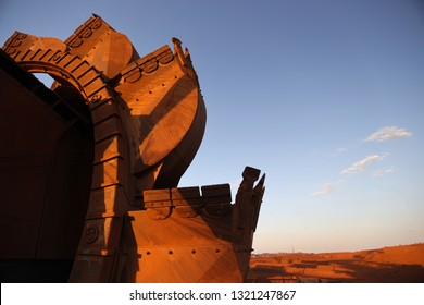 Close up pictures of mining reclaimer wheel bucket with sunrise at the back ground construction mine site Perth, Australia