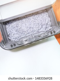 Close up piece of papers in paper shredder for recycling. Damaged paperwork in bin of shredder is the process of reusing paper material and save the world.