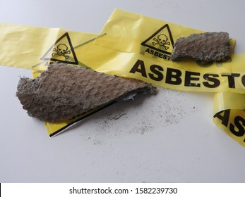 Close up of pieces grey asbestos and fibers. Old roof tiles and yellow barrier tape. Warning: caution health effects, hazard. Asbestos removal. Asbestosis or mesothelioma, part of a serie.