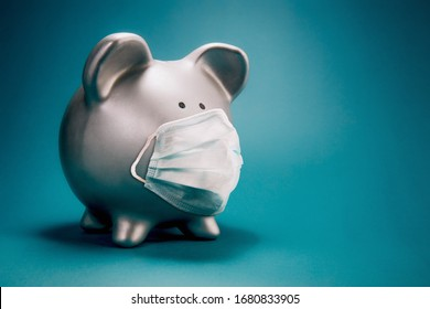 Close up of piggy bank, wearing protective face mask, isolated on blue background. Money saving concept in time of coronavirus pandemic. - Shutterstock ID 1680833905