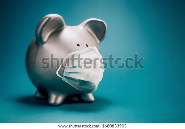 Close up of piggy bank, wearing protective face mask, isolated on blue background. Money saving concept in time of coronavirus pandemic.