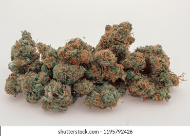 Close up of a pile of 2 different kinds of marijuana buds mixed together against a white background.