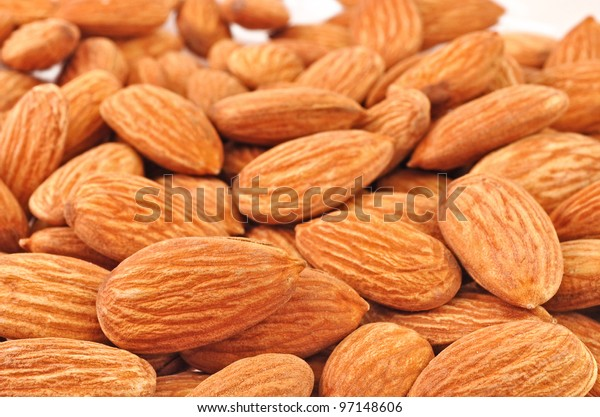 close up of pile of almonds piled on white