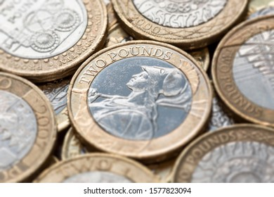 """Close up of a pile of British Two Pound Coins with selective focus on the words """"Two Pounds"""""""
