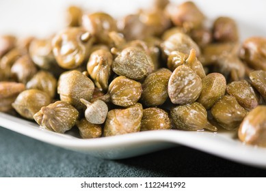 close up of pile of capers on white plate