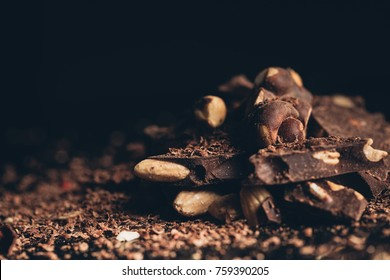 Close up of Pile of dark chocolate with nuts pieces on a black