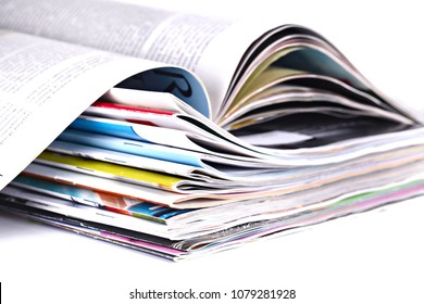 Close up pile of magazines on white background, shallow focus