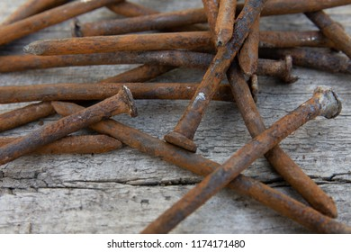 Close up pile of old rusty bent nails resting on wood