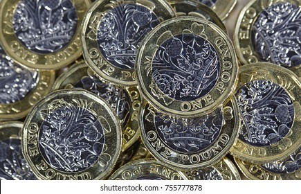 Close up of a pile of one pound coins in a horizontal format