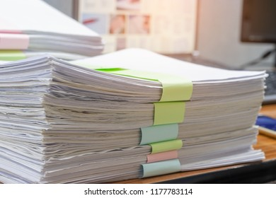 Close up pile of unfinished homework assignment stacked in archive with colorful papers on teacher's table waiting to be managed and inspected. Stack of paperwork. Education and business concept.