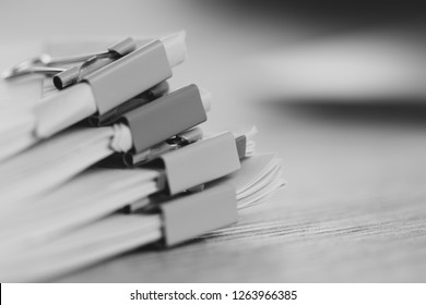 Close up pile of unfinished homework assignment stacked in archive with binder paper clips on table in school waiting to be managed and inspected. Stack of paperwork. Education and business concept.