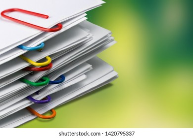 Close up pile of unfinished homework assignment stacked in archive with colorful paper clips on table in school waiting to be managed and inspected. Stack of paperwork. Education and business concept