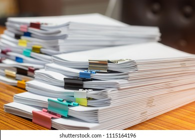 Close up pile of unfinished paperwork on office desk waiting to be managed. Stack of homework assignment with paperclips. Report papers stacks. Business and education concept.