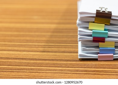Close up pile of unfinished paperwork on office desk waiting to be managed and inspected. Stack of homework assignment with colorful paper clips. Report papers stacks. Business and education concept.