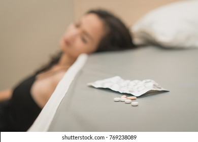 close up pills on the bed. Stressed female taking drug overdose sitting beside the bed try to suicide.