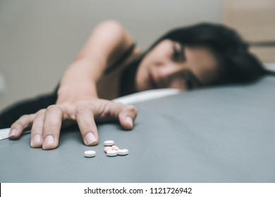 close up pills in young women hands. Stressed female taking drug overdose sitting beside the bed try to suicide.